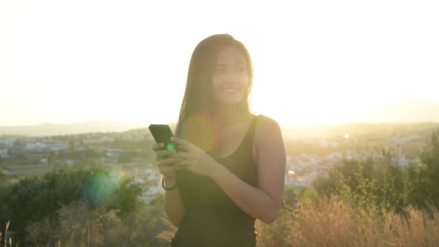 Young Happy Asian Tourist Woman Thinking While Using Phone On The Hill