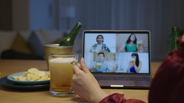 若い幸せなアジアの女性は、ビデオ通話を介して飲んでガラスとボトルショービールフォームでビールを注ぐ自宅で友人とリラックスナイトパーティーイベントオンラインお祝いを楽しみま� - 人里離れた点の映像素材/bロール