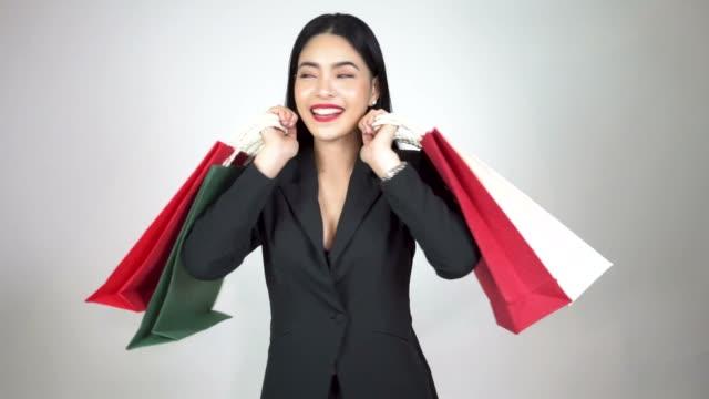 unga glada asiatisk kvinna håller en massa kassar och sväng runt på vit bakgrund - köpnarkoman bildbanksvideor och videomaterial från bakom kulisserna