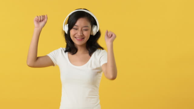 young happy asian woman listening to music on headphones and dancing - maglietta bianca video stock e b–roll