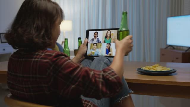 若い幸せな魅力的なアジアの女性は、オンラインビデオ通話を介して飲んでガラスとボトルトーストでビールの歓声と自宅で友人とリラックスナイトパーティーイベントオンラインお祝いを� - 人里離れた点の映像素材/bロール