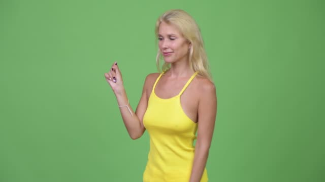 Young happy beautiful blonde woman snapping fingers and showing something Studio shot of young beautiful woman with blond hair against chroma key with green background snapping stock videos & royalty-free footage