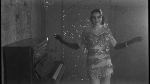 Young happy beautiful woman in bright sparkling luxury silver dress, smiles gown fluttering dances in room near piano, black and white old fashioned film with added noise. 20s stylized carnival party