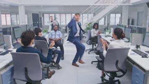 vídeos y material grabado en eventos de stock de joven feliz gerente de negocios usando un traje y corbata bailando en la oficina. los colegas están alentando. la gente de negocios diversa y motivada trabaja en las computadoras en la oficina abierta moderna. - bailar