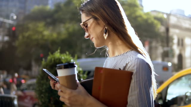 Young happy businesswoman with coffee and documents using smartphone in downtown in sunny day. Slow motion video