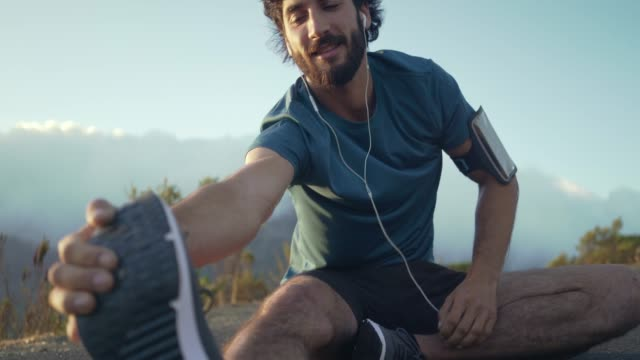 Young happy caucasian brunette man in his athletic clothes preparing to do some exercise outside and stretching his legs whilst sitting down Young happy caucasian brunette man in his athletic clothes listening to music through his earphones and preparing to do some exercise outside by stretching his legs whilst sitting down on the road athleticism stock videos & royalty-free footage