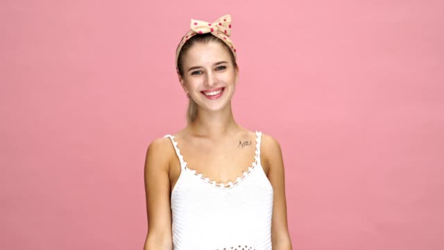 Young happy caucasian lady smiling and showing peace gesture over pink background. video