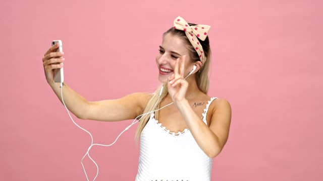 Young happy caucasian lady talking with friends by phone over pink background. video