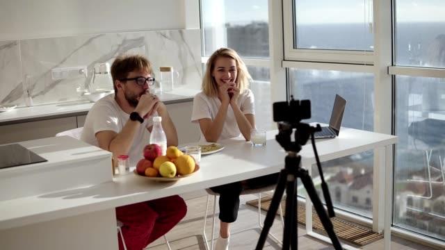 Junge glücklich paar Blogger im Gespräch mit der Kamera. Frühstück, während Video-Chat auf der Kamera aufzeichnen. sprechen auf Kamera zu Hause Skype Technologie fröhliche Menschen Diskussion Blog Webcam, Online-Video – Video