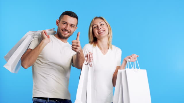 Young happy couple holding shopping bags, man showing thumbs up sign on blue background