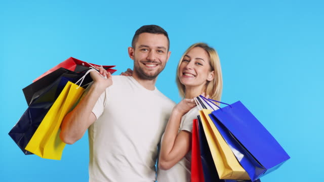 Young happy couple holding shopping bags showing thumbs up sign on blue background