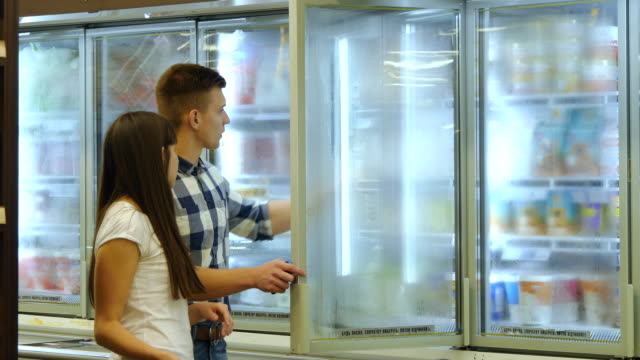 Young happy couple is standing by the freezer in grocery store and picking packages with frozen food. Man taking product from the fridge and smiling video