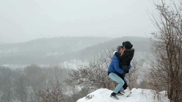 Young happy couple kissing and hugging in the winter snowy forest video