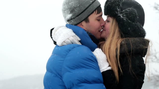 Young happy couple kissing in the winter snowy forest video