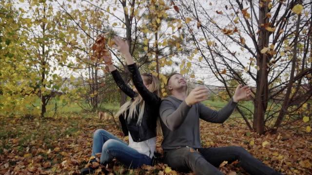 unga lyckliga paret spelar och kasta löv i parken hösten - gå tillsammans bildbanksvideor och videomaterial från bakom kulisserna