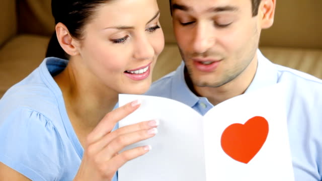 Young happy couple reading greeting card together at home video