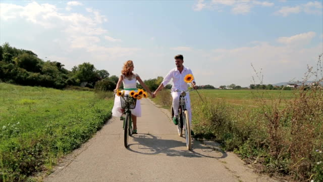 Young happy couple riding bicycles in countryside. video