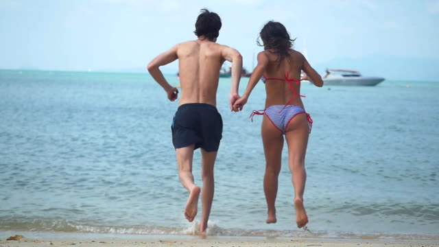 Young happy couple running into tropical sea in slow motion. 1920x1080 video