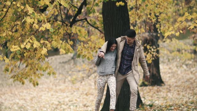 stockvideo's en b-roll-footage met jonge gelukkige paar wandelen omarmd tijdens herfst dag in het park. - s