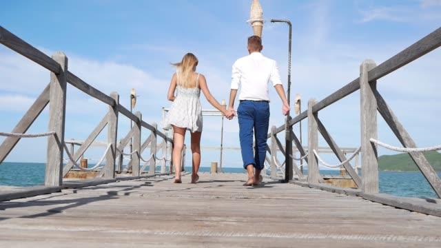 mavi gökyüzü arka plan üzerinde ahşap bir iskele üzerinde yürüyen genç mutlu çift. romantik kavramı. hd, 1920 x 1080. - dalgakıran stok videoları ve detay görüntü çekimi