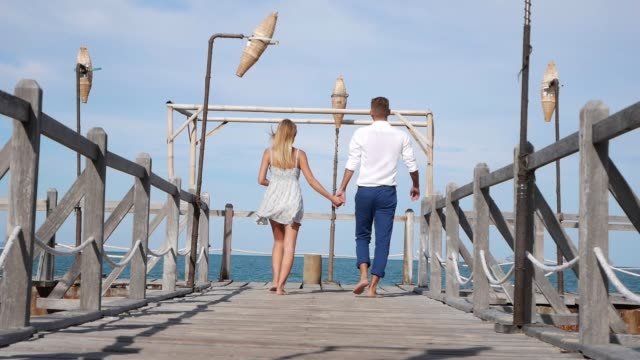 young happy couple walking on a wooden pier on the blue sky background. romantic concept. hd, 1920x1080. - molo video stock e b–roll
