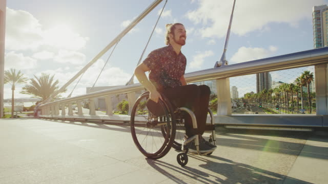 Young happy disabled man pushing wheelchair across bridge in city with lens flare 4k young happy disabled man pushing wheelchair across modern bridge in downtown city environment on sunny day wheelchair stock videos & royalty-free footage