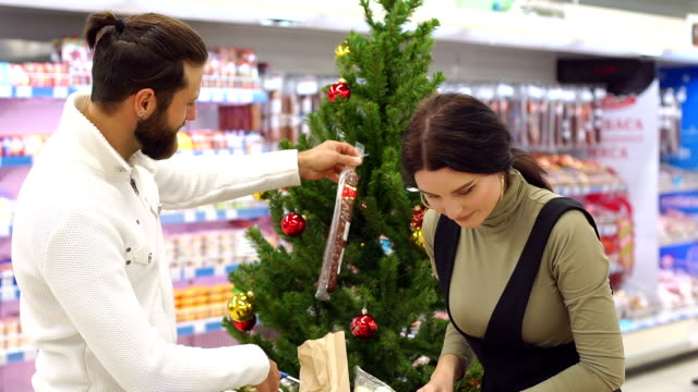 Young happy family buying groceries at supermarket for Christmas.