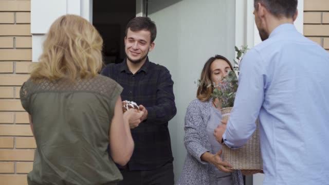 stockvideo's en b-roll-footage met jonge gelukkige familie staan bij deuren en wachten op hun buren - buren