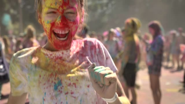 vídeos de stock e filmes b-roll de young happy girl in colourful powder is jumping and screaming on holi festival in daytime in summer, color concept - holi