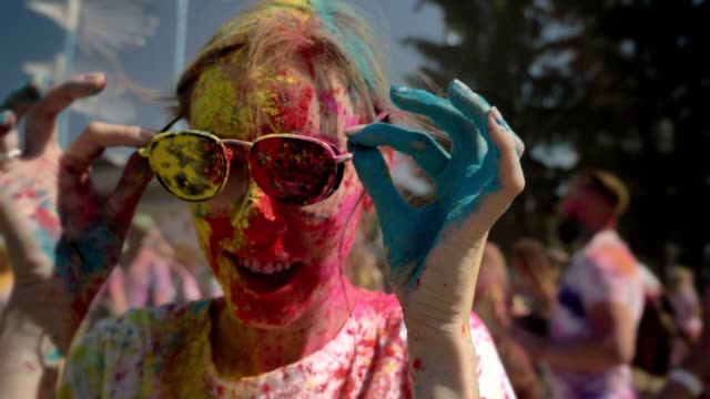 vídeos de stock e filmes b-roll de young happy girl in colourful powder is wearing sunglasses on holi festival in daytime in summer, color concept - holi