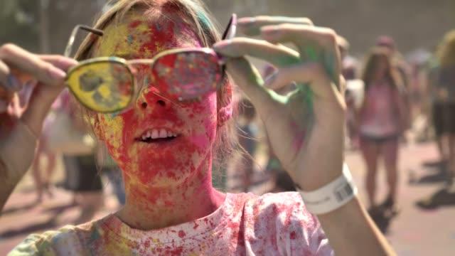 glückliches mädchen in bunten pulver trägt sonnenbrille und anfängt zu lachen auf holi-fest in der tageszeit im sommer, farbkonzept - musikfestival stock-videos und b-roll-filmmaterial
