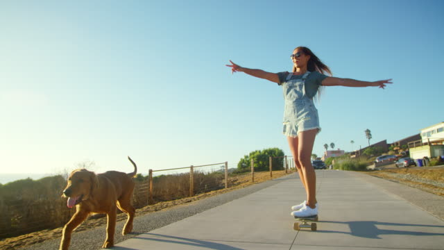 Young happy girl skateboarding with dog at sunset