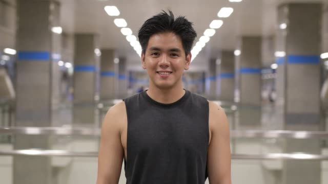 Homem asiático considerável feliz novo que sorri na estação de metro - vídeo