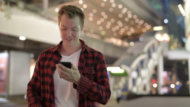 ung glad hipster man tänker och använder telefon i staden på natten - endast en man i 30 årsåldern bildbanksvideor och videomaterial från bakom kulisserna