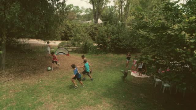 glückliche kinder summer camp spielen fußball in grasgrün feld kinder zeitlupe antenne vertikal - ferienlager stock-videos und b-roll-filmmaterial