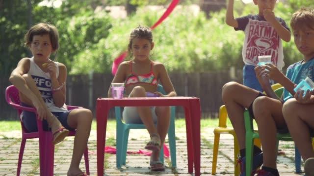 junge glückliche kinder im sommerlager sitzen bunte kunststoff stühle trinken essen snacks spaß außerhalb im grünen rasen feld kinder partei zeitlupe - ferienlager stock-videos und b-roll-filmmaterial
