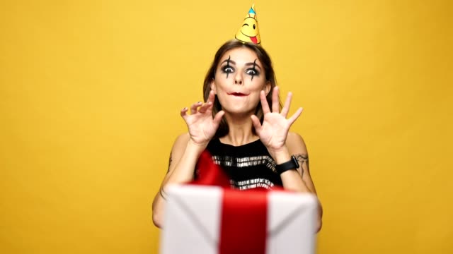 Young happy lady with halloween make up and holiday cap getting present and dance with it isolated over yellow video