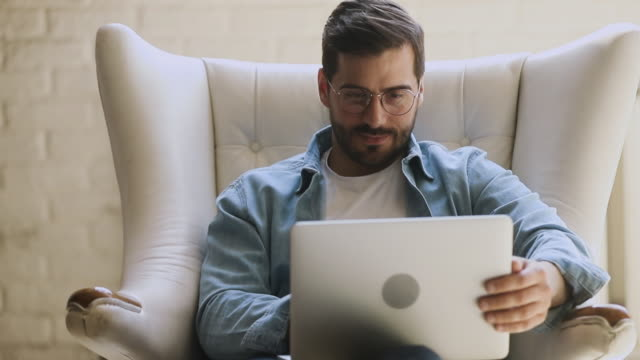 Young happy man sit on chair using laptop relaxing laughing Young happy man sit on comfortable chair using laptop relaxing working laughing, smiling guy wear glasses enjoying spending time with computer having fun online chatting with friends in social media lounge chair stock videos & royalty-free footage