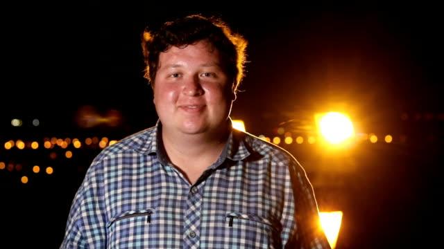 ung lycklig man leende utomhus på natten, porträtt - endast en man i 30 årsåldern bildbanksvideor och videomaterial från bakom kulisserna