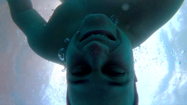 Young happy man swims under water in the pool. Portrait of smiling guy drowning underwater and looking at camera. Air bubbles out of his mouth. Sinking of male swimmer. Concept of selfie. Slow motion