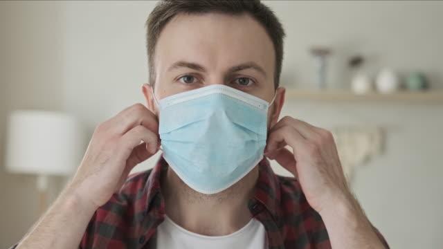 junge glückliche mann aus der medizinischen maske und blick auf die kamera in innenräumen - entfernt stock-videos und b-roll-filmmaterial
