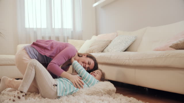 Young happy mother tickling her daughter and having fun on the carpet. video