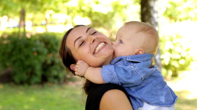 vídeos de stock, filmes e b-roll de uma jovem mãe feliz caminha com seu filho recém-nascido no parque no verão. - novo bebê