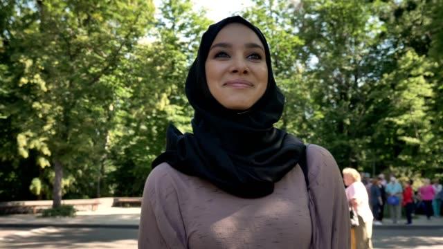 vidéos et rushes de jeune fille musulmane heureuse en hijab est souriant et aller à l'université dans la journée dans le concept de l'été, religieux, étude concept - femme seule s'enlacer