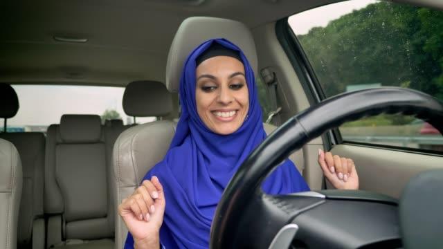 自律操縦無人車の自動運転のステアリング ホイールの後ろに座ってヒジャーブの若い幸せなイスラム教徒の女性 - 自動運転車点の映像素材/bロール