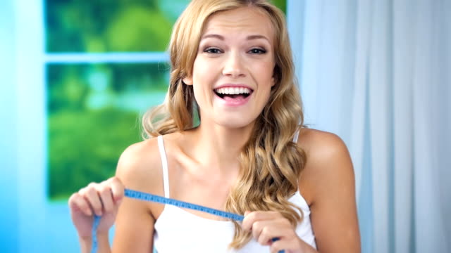 Young happy smiling woman measure tape, at home video