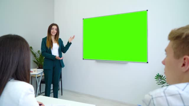 young happy teacher near with a green screen board teaching students in classroom