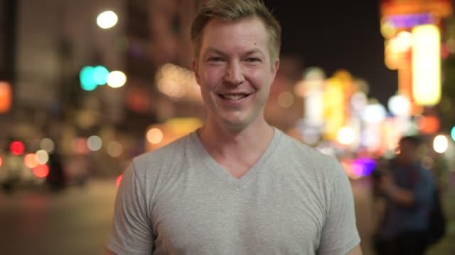 Jovem turista feliz sorrindo contra a vista das ruas em Chinatown à noite - vídeo