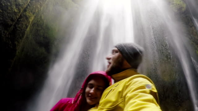 Young happy traveling couple taking a selfie on gopro camera. Man and woman near the Gljufrabui waterfall in Iceland video