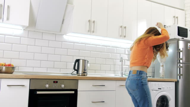 young happy woman dancing in kitchen and having some fun - jeans video stock e b–roll